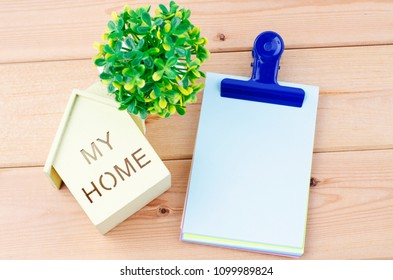 Template background for mortgage concept,Wooden home replica and blank notepad on wooden desk