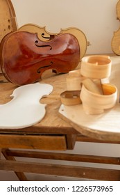 Template for Cello and wood shaving curls on table, and finished Cello or, violoncello, in background of musician's craftsman workshop