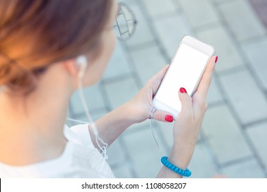 Template of a close up on a woman's hands, holding a phone while wearing headphones. Communicate inside the copy space about phone applications, music listening, street style, youth