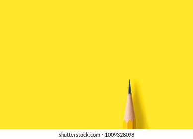 Template with copy space by top view close up macro photo of wooden yellow pencil isolated on yellow paper that look minimalist and clean. Flash light made smooth shadow from yellow pencil.