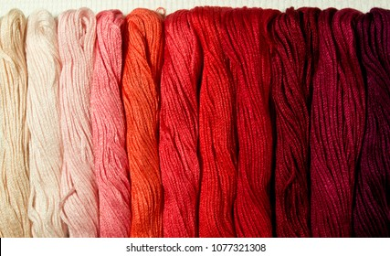 Template for design of background for website , blog, article or advertisement about hobby cross stitch. Bright colored skeins of thread mouline in red color and shades from pale pink to maroon.
