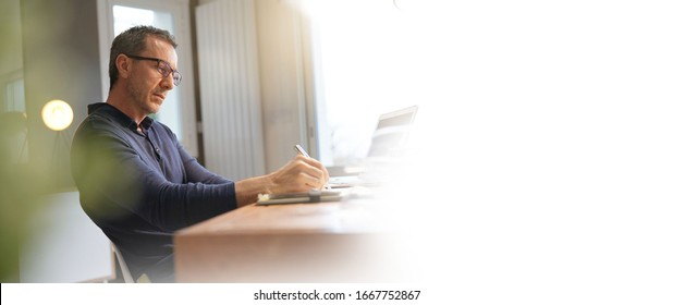 Template middle-aged guy having hot drink, working on laptop