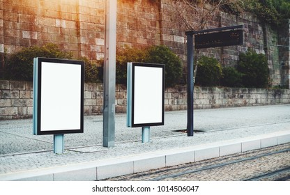 Template of two empty city billboards on train station outdoors or metro station; mock-up of blank informational banners in urban settings near tram stop with electronic indicator panel behind