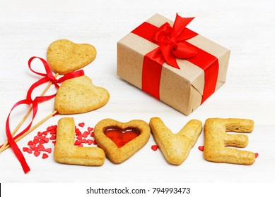 "Template for Valentine's Day. Box with a gift wrapped in paper and tied with a red ribbon and homemade cookies in the shape of hearts and letters ""LOVE"", red heart-shaped decoration. White wooden ba"