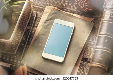 Template of white smartphone on the table with notes and old books. Clipping path