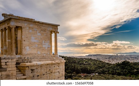 The Temple of Athena Nike, on the Acropolis of Athens, Greece, named after the Greek goddess Athena. Philopappos Hill and Piraeus is in the background.