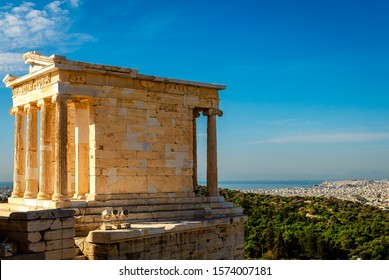 The Temple of Athena Nike, on the Acropolis of Athens, Greece, named after the Greek goddess Athena. Philopappos Hill, Piraeus and the saronic gulf are in the background.