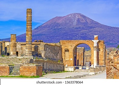 Temple columns and gate with Vesuvius volcano in the background  at the ancient Roman city of Pompeii, Italy