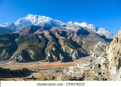 A temple complex in Manang Annapurna Circuit Trek, Nepal. Stupa in front of other buildings. Temple built on a rocky mountain hills. Sacred place for many Buddhist tourists. Dry land. Clear sky.