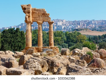 Temple of Dioscuri (Castor and Pollux) with Agrigento town in the Background. Famous ancient ruins in Valley of Temples, Agrigento, Sicily, Italy. UNESCO World Heritage Site.
