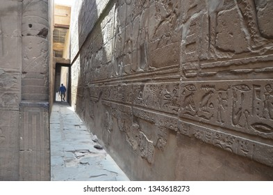 The Temple of Edfu is an Egyptian temple located on the west bank of the Nile in Edfu. It's considered to be one of the most beautiful and preserved Temples in Egypt. A man walking  out the temple