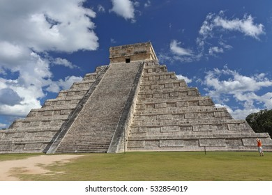 Temple of Kukulkan on blue sky background Chichen Itza. Mexico. Mayan people architecture. A little figure of the photographer next to the temple emphasizes the greatness of ancestor creation.