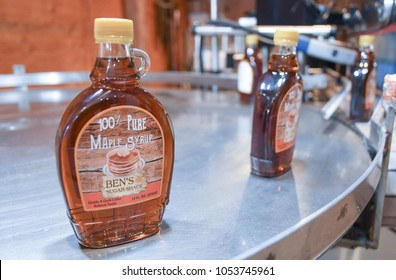 Temple, N.H./USA - March 24, 2018: Bottles of maple syrup come off the line at Ben's Sugar Shack on Maple Weekend. Ben Fisk started tapping trees at age 5 and was making award-winning syrup by age 15.