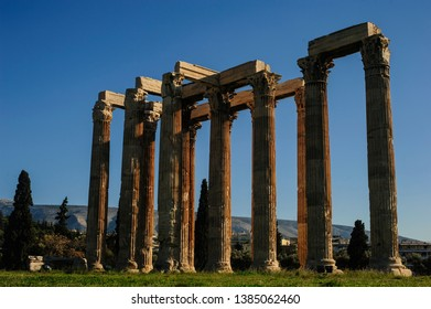 The Temple of Olympian Zeus in Athens, Greece shot against the mountain of Hymettos and bright blue sky.