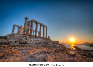 The Temple of Poseidon in Cape Sounion, Greece at sunset on a clear Summer day