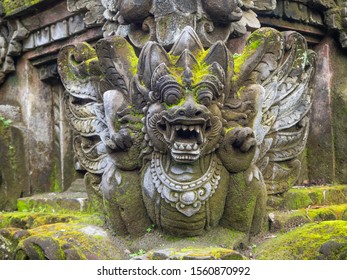 Temple with statues covered with moss on the island of Bali