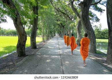 Temple in Tinh Bien district at An Giang province, Viet Nam - September 23, 2018:  Monks with begging bowls beneath saffron robes go out in the morning in West Vietnam