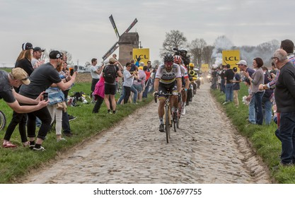 Templeuve, France - April 08, 2018: Peter Sagan of Bora-Hansgrohe Team, leading the race on the cobblestone road in Templeuve in front of the traditional Vertain Windmill during Paris-Roubaix 2018