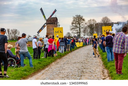 Templeuve, France - April 08, 2018: The spectators are waiting for the peloton on the cobblestone road in Templeuve in front of the traditional Vertain Windmill during Paris-Roubaix 2018.