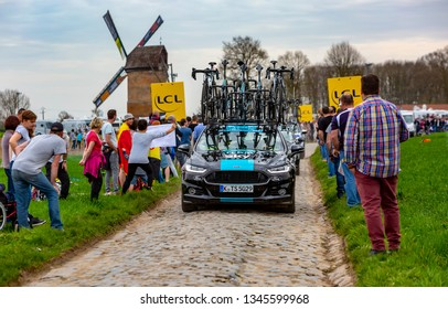 Templeuve, France - April 08, 2018: The car of Team Sky driving on the cobblestone road in Templeuve in front of the traditional Vertain Windmill during Paris-Roubaix 2018.