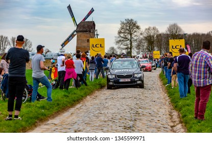 Templeuve, France - April 08, 2018: The car of BMC Team driving on the cobblestone road in Templeuve in front of the traditional Vertain Windmill during Paris-Roubaix 2018.