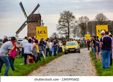 Templeuve, France - April 08, 2018: The car of Lotto-Jumbo Team driving on the cobblestone road in Templeuve in front of the traditional Vertain Windmill during Paris-Roubaix 2018.