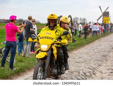Templeuve, France - April 08, 2018: The yellow bike of Mavic driving on the cobblestone road in Templeuve during Paris-Roubaix 2018.