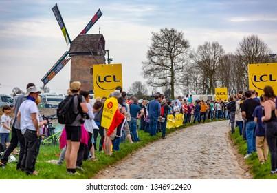 Templeuve, France - April 08, 2018: The spectators are waiting for the peloton on the cobblestone road in Templeuve during Paris-Roubaix 2018.