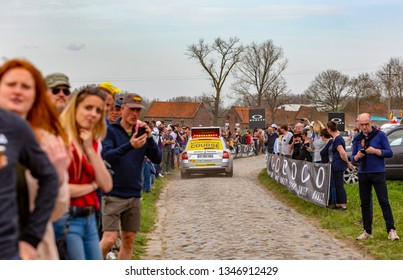 Templeuve, France - April 08, 2018: The official Race Information car driving on the cobblestone road in Templeuve in front of the specators during Paris-Roubaix 2018.
