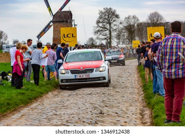 Templeuve, France - April 08, 2018: The car of Sport Wieler Magazine driving on the cobblestone road in Templeuve in front of the traditional Vertain Windmill during Paris-Roubaix 2018.