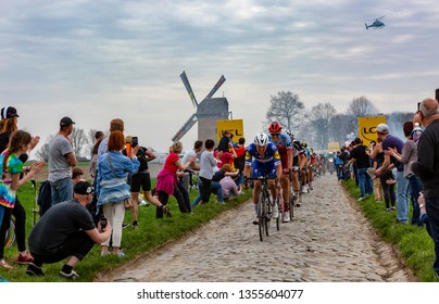 Templeuve, France - April 08, 2018: The peloton riding on the cobblestone road in Templeuve in front of the traditional Vertain Windmill during Paris-Roubaix 2018.