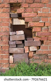 Temporarily repaired hole in an old brick wall; Unprofessional and cheap repair of old masonry; Neglected building