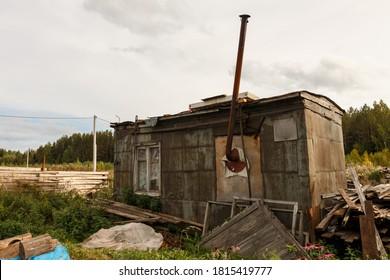 Temporary garden house. A metal trailer with a pipe in the garden.