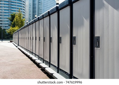 Temporary lavatories placed in a row in a park for a sport event.