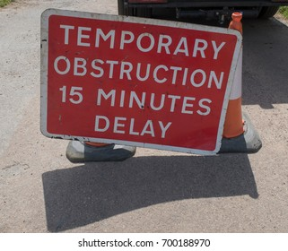 """Temporary Obstruction 15 Minute Delay"" Road Sign for Mobile Roadworks on a Country Lane in Rural Devon, England, UK"
