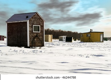 """Temporary shacks used for ice fishing situated on the frozen """"Red River"""" in Manitoba."""