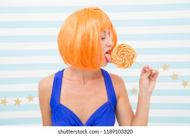 temptation of sexy crazy girl while licking lollipop candy. desire and temptation. sweet temptation. say no to unhealthy food. crazy girl feeling temptation about orange lollipop candy