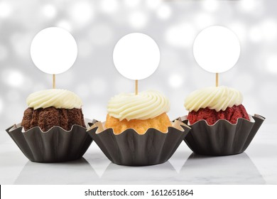 A tempting cupcake topper mockup featuring three delicious gourmet cupcakes on a white marble background. Add your own design to the cupcake toppers.