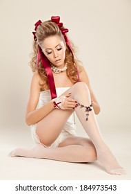 A tempting  young woman  in the doll style with red bow and red shoes  sitting on the floor.Studio photography.The main focus is on the necklace.