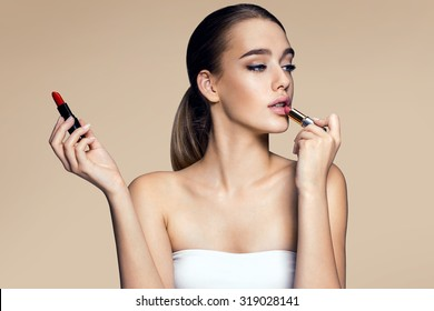 Tempting young woman with lipstick. Photography of mixed race Brazilian brunette woman on beige background