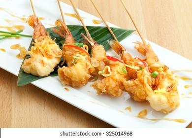 Tempura jumbo shrimp skewers on a white plate.