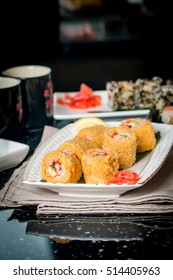 Tempura Maki Sushi - Deep Fried Roll made of Crab Meat, Avocado and Eel inside. Served on White Plate on Black table