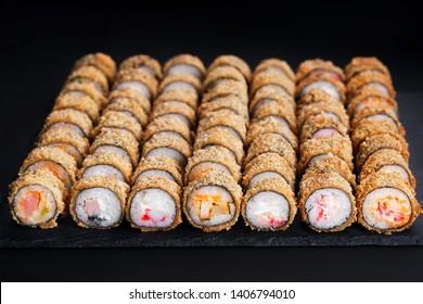 Tempura maki sushi rolls set on black slate. Japanese traditional fusion food style, restaurant menu background, degustation, buffet