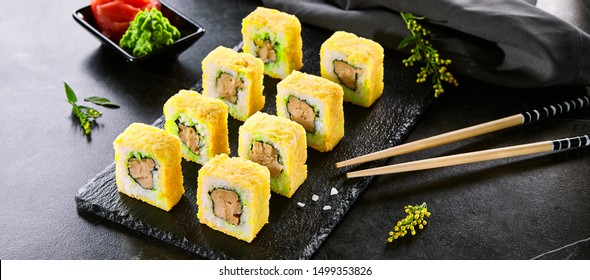 Tempura roll traditional Japanese dish. Sushi with raw salmon, eel and cucumber. Asian food and chopsticks on black plate. Japan restaurant meal concept. Modern gourmet food, delicious dinner