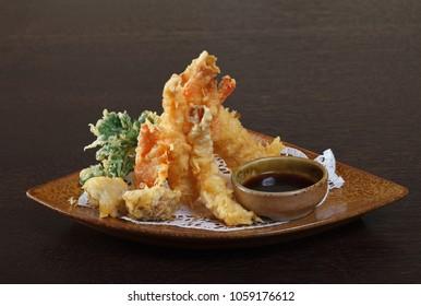 Tempura shrimps (deep fried shrimps) with soy sauce on wooden background.