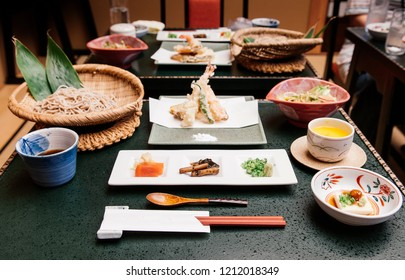 Tempura Zaru cold Soba set with Tofu, Gobo root, sauce and wasabi in ceramic plate and bowl on black table