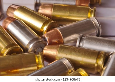 Ten 40 caliber hollow point in a pile some with brass cases and the others are silver