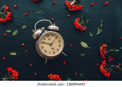 Ten after ten on alarm clock, flat lay top view minimal composition of timepiece placed on dark wooden background with retro floral arrangement