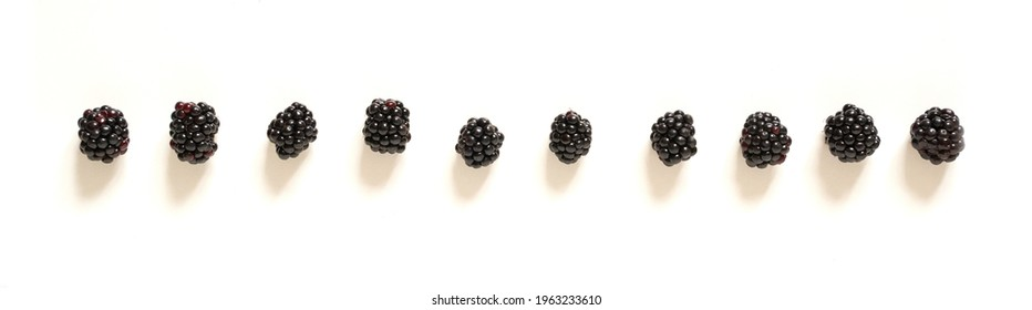 Ten blackberries on an isolated white background. Social distance concept.