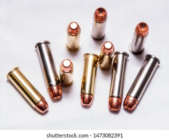 Ten bullets, five .38 special full metal jacket and fice .357 magnum ones on a white background